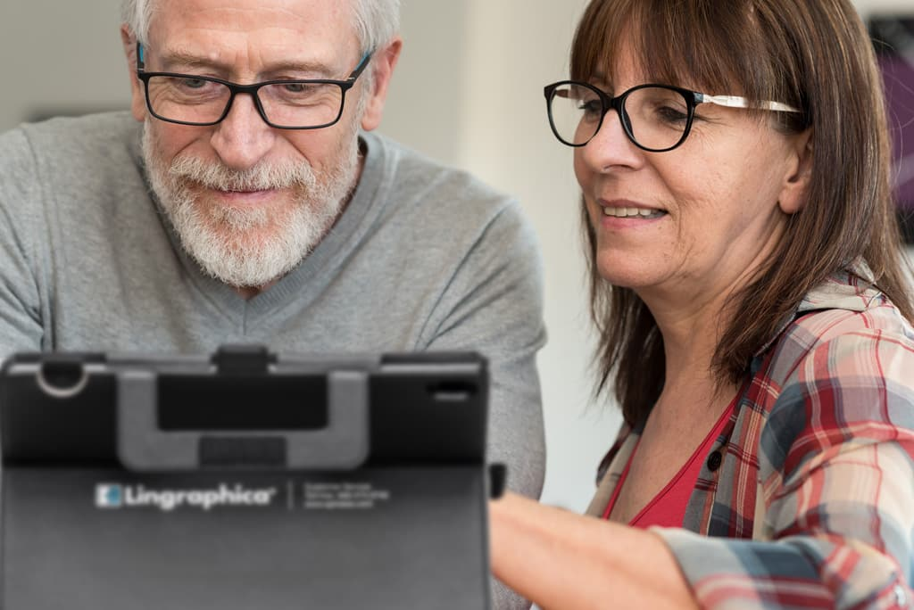 Male person with aphasia using a Lingraphica TouchTalk speech-generating device with his caregiver