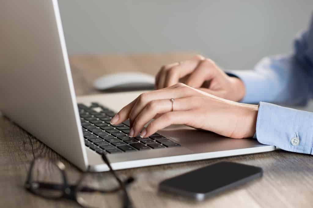 Woman's hands typing on a laptop computer keyboard