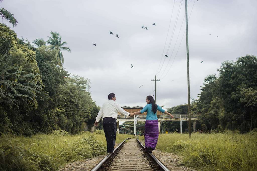 couple with back to camera walking along train tracks holding hands