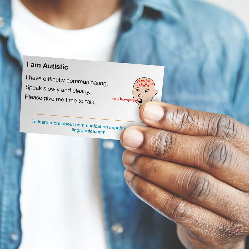"Man holding communication ID card that says, ""I am autistic. I have difficulty communicating. Speak slowly and clearly. Please give me time to talk."""